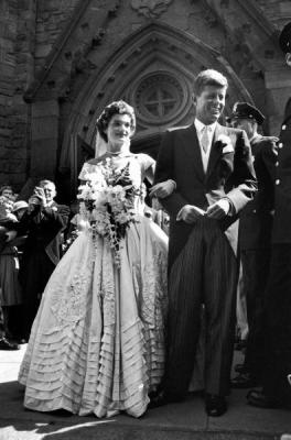 Jacqueline Bouvier with her husband Sen. John Kennedy as they stand in front of church after wedding ceremony.